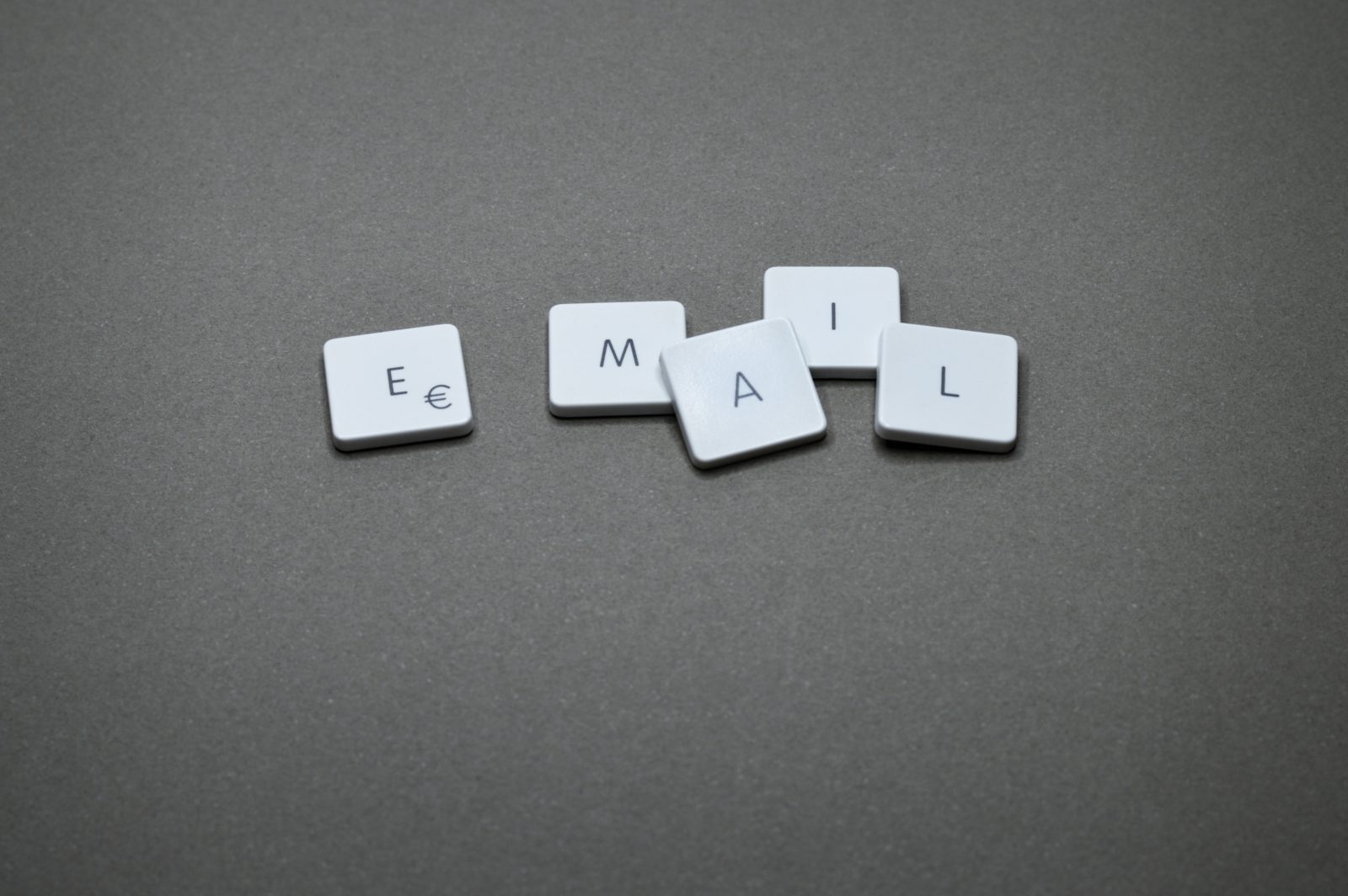 Email marketing tips for small businesses showing white tiles that spell email on a grey surface